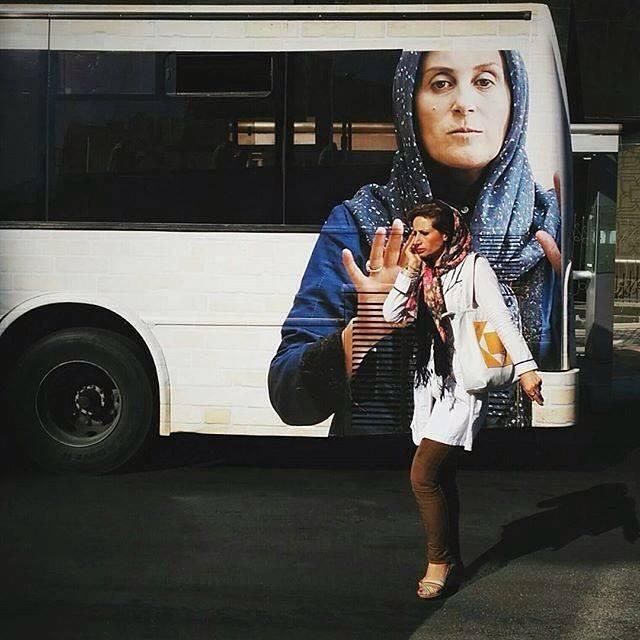 A woman passes by a public bus